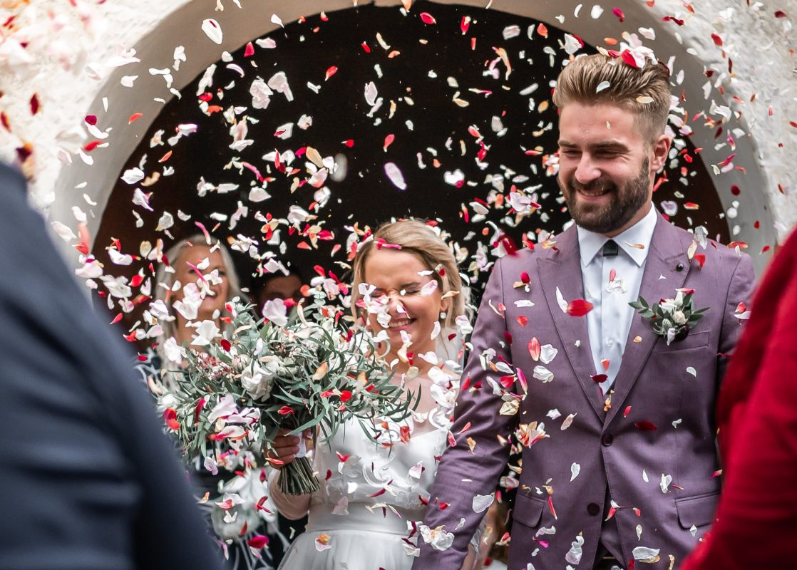 confetti being thrown over wedded couple